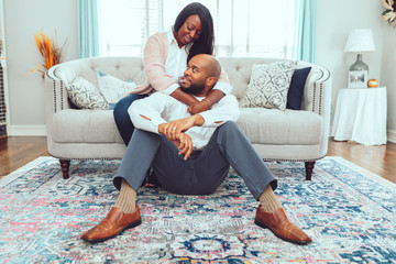 Woman embraces man on couch as he sits on the floor in their home