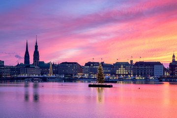 Sunset in Hamburg. Panoramic view of the decorated city center from Alster Lake, view to Hamburg Rathaus and a christmas tree installed in the center of the lake. Atmosphere before the New Year.