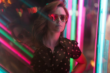 Cinematic night portrait of girl with sunglasses and neon lights