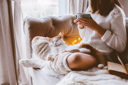 Girl reading a book and drinking warm cocoa on a sofa