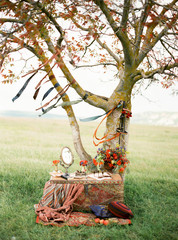 A vintage chest with a mirror, flowers and colourful fabrics with a tree behind