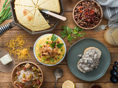 Full spread of Southern United States heart foods. Gumbo, black-eyed peas, jalapeno cornbread, shrimp and grits, and biscuits and gravy,