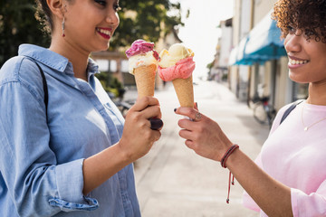 Two female friends eating ice cream outdoor