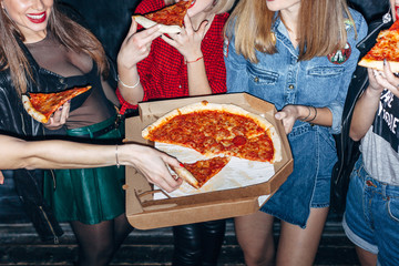 Group of young beautiful women fave fun together at night eating pizza and smiling casual style