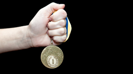 Woman hand holding gold medal against black background. Award and victory concept