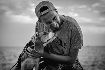 Black and white photo of a guy with a dog on the beach