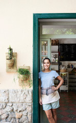 Pretty waitress with apron in doorway of cafe.