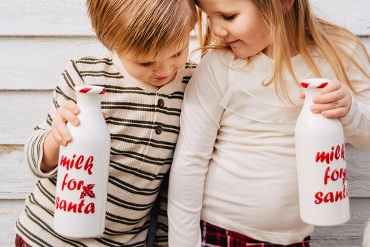 Toddler siblings dressed up for Christmas drinking milk from festive jars.