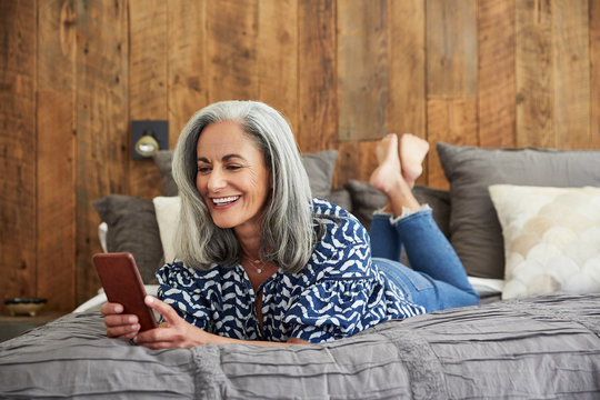Mature woman with grey hair texting on her mobile phone smiling