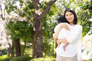 portrait of young asian mother and baby in park