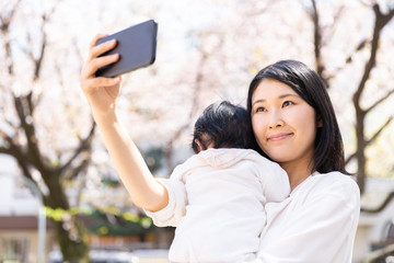 portrait of young asian mother and baby looking cherry blossom