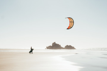 Kitesurfer walking on the beach