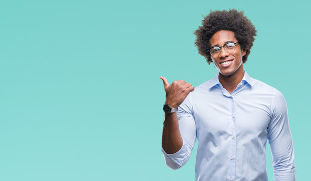 Afro american business man wearing glasses over isolated background smiling with happy face looking and pointing to the side with thumb up.