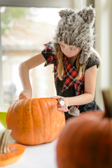 Girl scooping out inside of a pumpkin