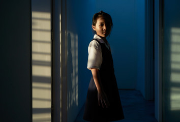 Little Asian girl stand alone in house . Sunset light shining pass through the window.