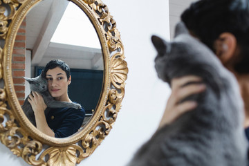 Brunette woman with her cat looking at the mirror