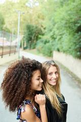 Tender girlfriends posing on street