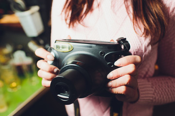 Girl with vintage camera in the hands.