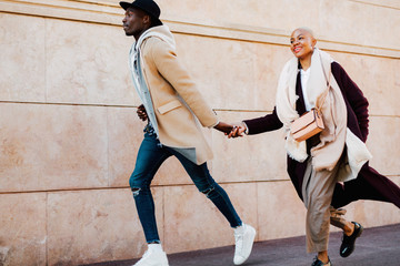 Cool multiethnic couple holding hands running on the street.