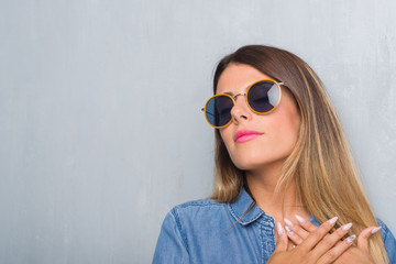 Young adult woman over grunge grey wall wearing retro sunglasses smiling with hands on chest with closed eyes and grateful gesture on face. Health concept.