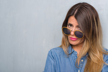 Young adult woman over grunge grey wall wearing retro sunglasses skeptic and nervous, disapproving expression on face with crossed arms. Negative person.