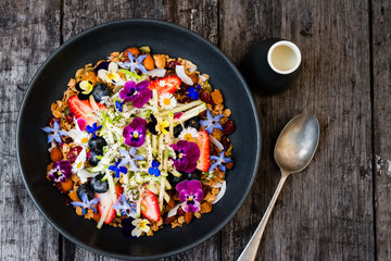 a pretty bowl of granola with oats, fruit, nuts, and flowers