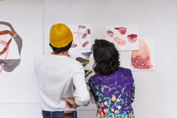 Artists Analyzing Illustrations Stuck On Wall In Studio