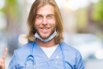 Young handsome doctor man with long hair over isolated background showing and pointing up with fingers number two while smiling confident and happy.