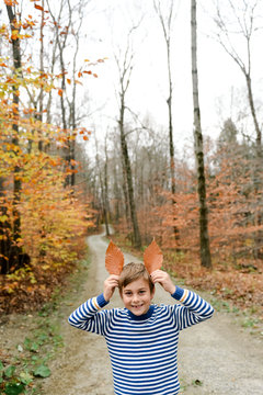 little boy outside in the fall playing with leaves