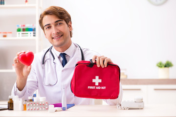 Young doctor with first aid kit in hospital