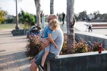 Father consoling hurt child at skatepark