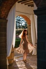 Lovely redhead girl swirling in sunset light