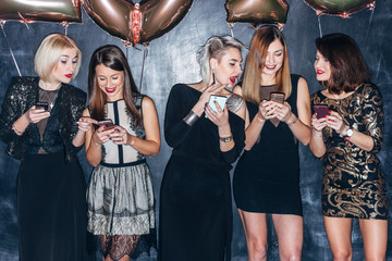 Group of five beautiful stylish night style women posing and chatting with mobile phones