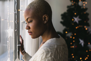 Closeup of a woman looking through the window on Christmas.