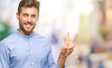 Young handsome man over isolated background smiling with happy face winking at the camera doing victory sign. Number two.