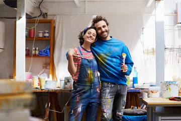 Artist Holding Paintbrush While Standing Arm Around Woman