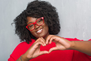 Young african american plus size woman over grey grunge wall wearing winter sweater smiling in love showing heart symbol and shape with hands. Romantic concept.