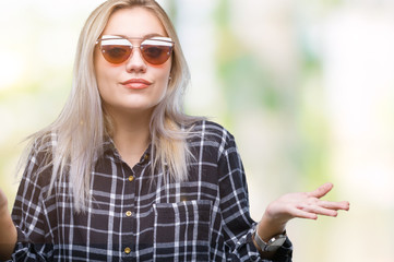 Young blonde woman wearing sunglasses over isolated background clueless and confused expression with arms and hands raised. Doubt concept.