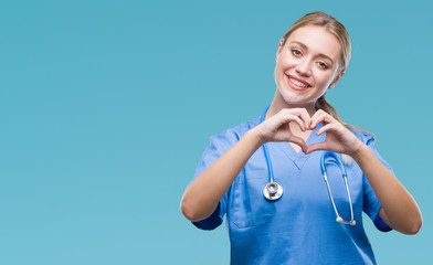 Young blonde surgeon doctor woman over isolated background smiling in love showing heart symbol and shape with hands. Romantic concept.
