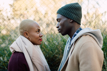 Cool multiethnic couple looking each other on the street in winter.