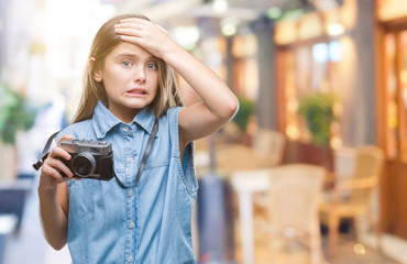 Young beautiful girl taking photos using vintage camera over isolated background stressed with hand on head, shocked with shame and surprise face, angry and frustrated. Fear and upset for mistake.