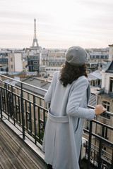 Young woman on a balcony with the Eiffel tower view