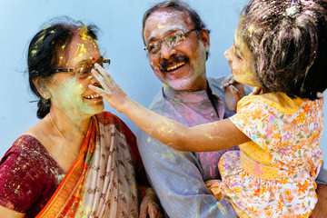 Little girl playing holi with her grandparents
