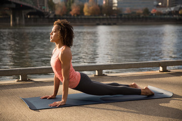 Mixed race female doing yoga on a waterfront