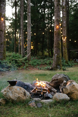 a campfire with a cast iron kettle