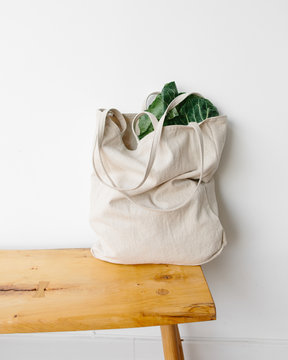 a linen bag full of green leafy vegetables