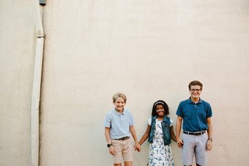 Multi-race siblings standing in front of a wall