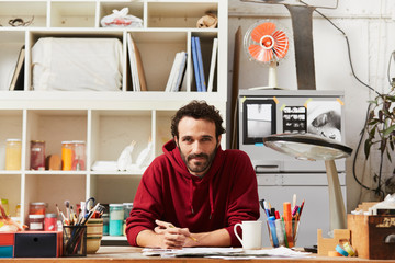 Confident Artist In Sweatshirt Painting While Sitting At Desk