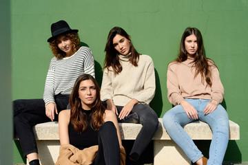 Stylish young women posing at camera