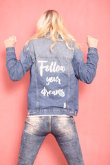 """one young woman, 20-29 years old, long blond hair. Shot in studio on pink background. Wearing jeans jacket with sign """"follow your dreams"""" on her back, (rear view)."""